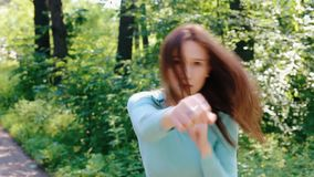 Het jonge meisje werkt slagen met haar handen uit stock footage