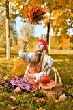 Het jonge meisje werpt een boeket van de herfstbladeren royalty-vrije stock foto