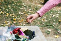 Het jonge meisje werpt een huisvuil in een vuilnisbak stock foto's