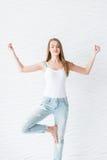 Het jonge meisje in wit hemd en blauw denim met gaten maakt meditatie op yogaoefening royalty-vrije stock fotografie