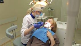 Het jonge meisje wit tanden in het tandbureau stock video