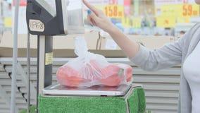 Het jonge meisje woog op de schalen van groene paprika's in de de lengtevideo van de supermarktvoorraad stock footage