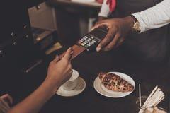 Het jonge meisje wordt berekend de koffie door creditcard stock afbeelding