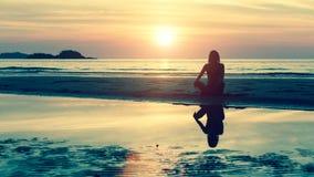 Het jonge meisje in yoga stelt zitting op het strand tijdens verbazende zonsondergang Royalty-vrije Stock Afbeelding