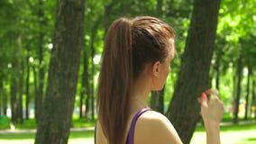 Het jonge meisje zet hoofdtelefoons in uw oren en het lopen stock footage