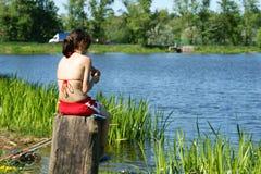 Het jonge meisje zit bij water en vissen Stock Foto