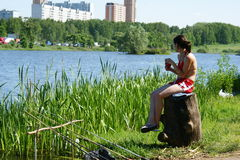 Het jonge meisje zit bij water en vissen Stock Fotografie