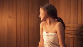Het jonge meisje zit bij het zweten en stoomruimte voor de behandeling van de huidzorg stock footage