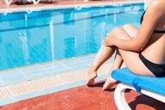 Het jonge meisje zit door het zwembad en beschermt haar huid met zonroom Zonbeschermingsfactor in vakantie, concept stock fotografie