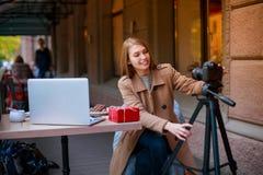 Het jonge meisje zit in een koffie met laptop, een giftdoos en een dessert en past de camera op een driepoot aan outdoors royalty-vrije stock fotografie