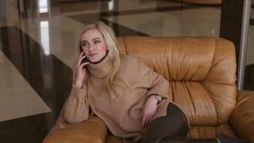 Het jonge meisje zit in een leunstoel in hotel met telefoon stock video