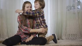 Het jonge meisje zit op de pluizige deken in de woonkamer en haar broer komt haar knuffelen Familieliefde en geluk stock videobeelden