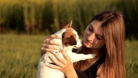 Het jonge meisje zit op een gazon in het park en kust haar hond stock footage