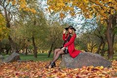 Het jonge meisje zit op een rots in een de herfstpark in een rode laag en zwarte hoed op haar hoofd stock fotografie