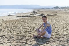 Het jonge meisje zit op het strand royalty-vrije stock afbeeldingen