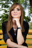 Het jonge meisje zit in park op een bank Stock Fotografie