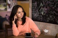 Het jonge meisje zit pensively in een koffie met een Kop van chocolade Stock Foto's