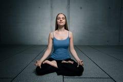 Het jonge meisje zitting en mediteren Royalty-vrije Stock Foto