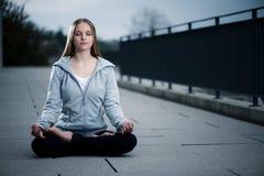 Het jonge meisje zitting en mediteren Royalty-vrije Stock Foto's