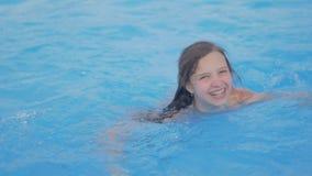 Het jonge meisje zwemt in zwembad Het tienermeisje geniet de zomer van vakantie op een zonnige dag in water van openluchtpool stock video