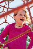 Het jonge meisjeskind spelen bij het openluchtspeelplaats netto beklimmen stock afbeeldingen