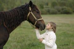 Het jonge meisjesmodel wrong zijn gezicht aan paard los Levensstijlportret Stock Fotografie