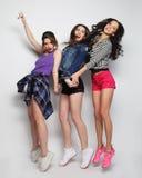 Het jonge meisjesvrienden dansen van vreugde in volledige lengte Stock Afbeeldingen