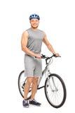 Het jonge mens stellen naast zijn fiets en het glimlachen royalty-vrije stock foto's