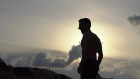 Het jonge mensenoverhemd van schreeuwen vrijheid en het slaan dient hoge heuvel van berg in zonsondergang in Mens die zijn handen stock footage
