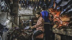 Het jonge mensenwerk hard in de leerfabriek binnen de dharavikrottenwijk in mumbay royalty-vrije stock fotografie