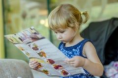 Het jonge menu van de meisjeslezing stock foto