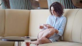 Het jonge model lounging op bank gebruikend smartphone en hebbend drank stock footage
