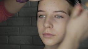 Het jonge model met natuurlijke schoonheid wordt klaar aan make-up stock videobeelden