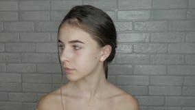 Het jonge model met natuurlijke schoonheid wordt klaar aan make-up stock footage