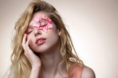 Het jonge model stellen voor modern tijdschrift met bloemblaadjes op gezicht stock foto