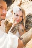 Het jonge modellenpaar stellen op het strand met stenen stock foto