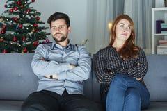 Het jonge moderne paar is geïrriteerd van Kerstmis stock fotografie