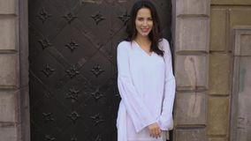 Het jonge modieuze gelukkige en het glimlachen vrouw stellen in stadsstraat stock videobeelden