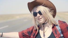 Het jonge modieuze meisje in cowboy kleedt het doen van lift in woestijn, op de weg Zij draagt rugzak en hoed pas stock videobeelden