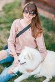 Het jonge modieuze meisje die van de hipstervrouw witte kid-skin hond in de kant van het land spelen royalty-vrije stock foto's