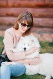 Het jonge modieuze meisje die van de hipstervrouw witte kid-skin hond in de kant van het land spelen stock fotografie