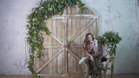 Het jonge modieuze meisje stellen tegen de houten poort, het glimlachen en het bekijken de camera royalty-vrije stock foto's