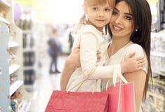 Het jonge moeder en dochter stellen in winkelcentrum stock afbeeldingen