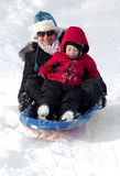 Het jonge moeder en zoons sledding onderaan een sneeuwheuvel royalty-vrije stock afbeeldingen