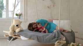 Het jonge moeder spelen met babydochter in bed stock videobeelden