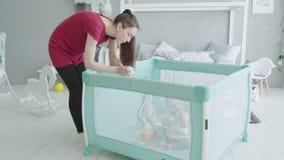Het jonge moeder spelen met babyzitting in box stock video
