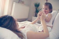 Het jonge moeder spelen met haar babymeisje in bed Royalty-vrije Stock Foto's