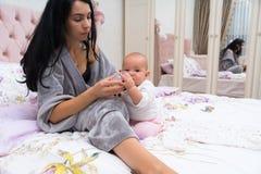 Het jonge moeder voorbereidingen treffen brengt voor haar baby met de fles groot royalty-vrije stock afbeelding