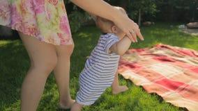 Het jonge moederonderwijs die eerst tot stappen maken haar babyzoon op gras bij binnenplaats stock video