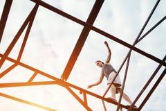 Het jonge moedige mens in evenwicht brengen op de bovenkant van hoge metaalbouw royalty-vrije stock afbeelding